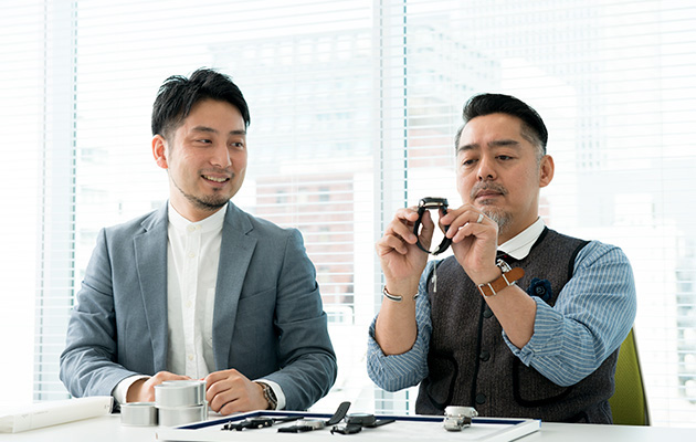 Photo of Monjugawa and Kishino staring at the watch