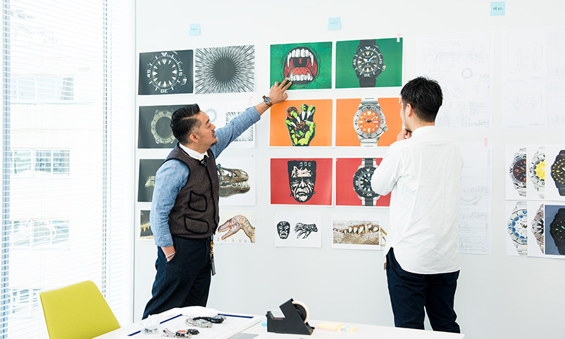 Monjugawa and Kishino comparing the monster illustration with the photo of the watches on the wall.
