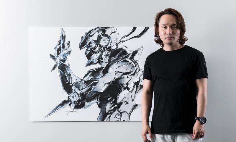 新川洋司氏とイラストボードの写真