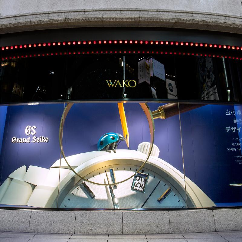 「和光本館」のショーウインドウの写真。巨大なグランドセイコー の上に青いてんとう虫が乗っている