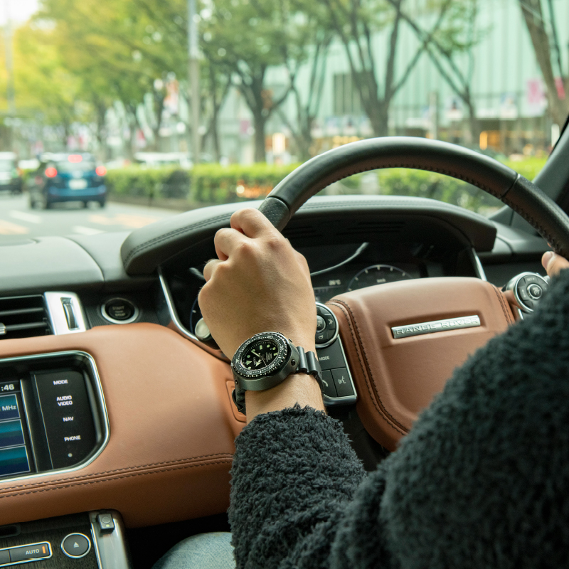 腕にダイバーズウオッチをつけて、車を運転する写真。