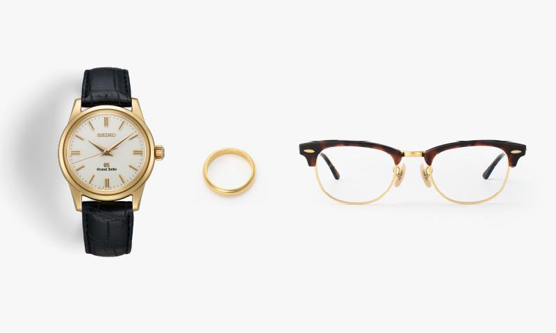 金色のグランドセイコー、金色の指輪、べっ甲と金縁の眼鏡を並べた写真
