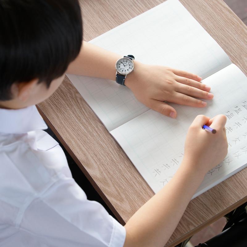 スクールタイムをつけて、漢字の練習をする小学生の写真