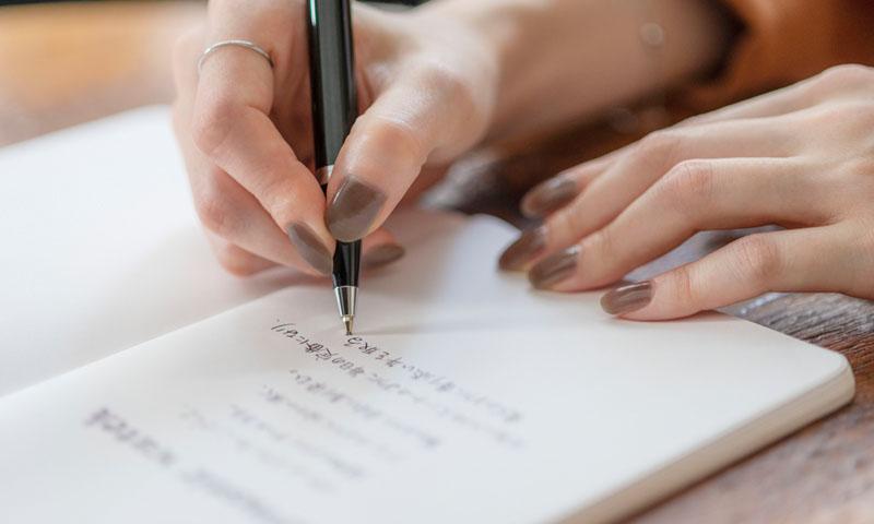 手帳に詩を書く手の写真